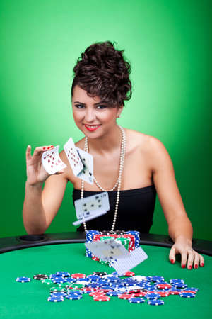 texas hold em: sexy casino woman playing with the cards, over green Stock Photo