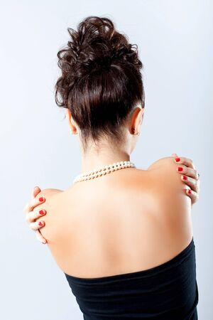 Back of sexy elegant woman, red nails, white necklace photo