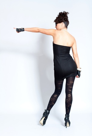 Back of fashion woman in sexy black dress, pointing at something photo