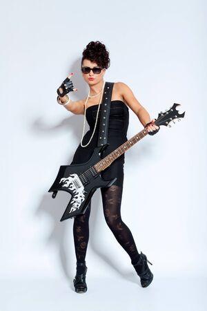 femme avec guitare: Sexy femme en robe noire tenant une guitare �lectrique, faire un signe de rock Banque d'images