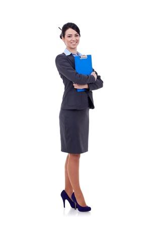 mujer cuerpo entero: Mujer de negocios de j�venes de larga duraci�n permanente con su portapapeles aisladas sobre fondo blanco