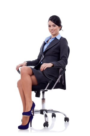 sitting on: Young business woman sitting on a chair isolated on white