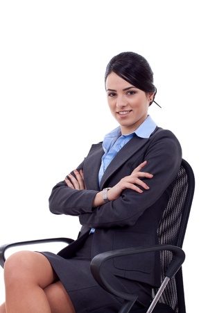 Attractive young caucasian business woman sitting in office chair with arms crossed. Isolated on white background photo