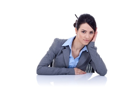 business woman sitting behind the desk looking a little tired and pensive, isolated on white Stock Photo - 9248387
