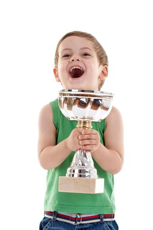 Portrait of a excited small boy holding a winners cup and screaming photo