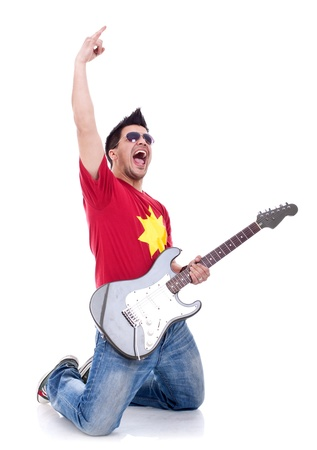 Attractive musician playing guitar on his knees and making a rock and roll gesture over white  Stock Photo - 9370384