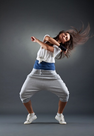 hiphop: young female dancing on the grey background, studio shot