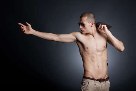 Artistic picture of a shirtless young male with sunglasses on a dark background photo