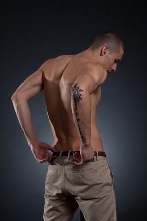 muscular male: Artistic picture of young male back on a dark background