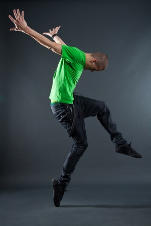 hip-hop style dancer posing on isolated grey background photo