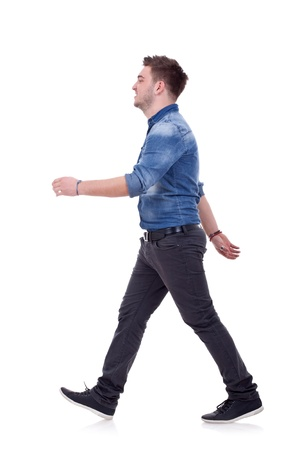 side view: side view of a young casual man walking forward over white Stock Photo