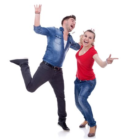 Portrait of an attractive young couple celebrating success with hands raised over white background Stock Photo - 9525323