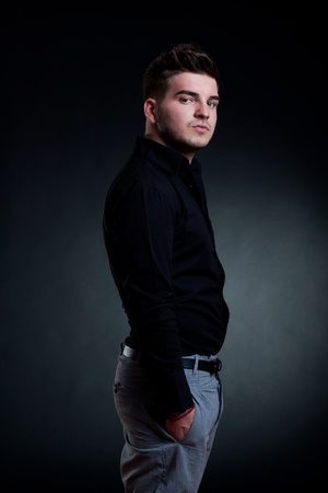 fashion picture of a man standing on a dark background Stock Photo - 9525680