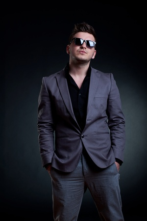 side pose: fashion picture of a man with sunglasses standing on a dark background