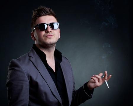 superiors: young man smoking a cigarette and having a superior attitude