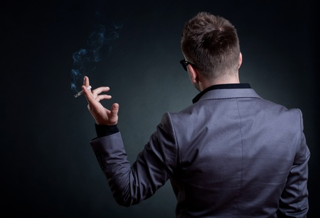 Back of a man with a cigarette in his hand, over dark background photo