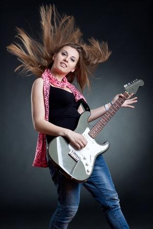 guitar player: headbanging woman guitarist playing her guitar over dark background Stock Photo