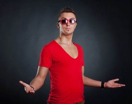fashion picture of a man standing on a dark background with his arms open Stock Photo - 9525964