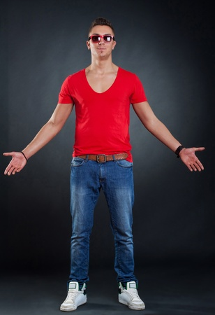 full lenght: Stylish young man with his arms open, on dark background
