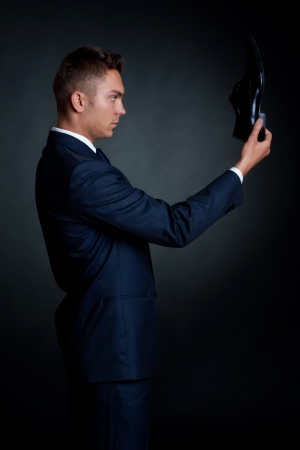 portrait of a stylish man in an elegant suit and shoes in hand  photo