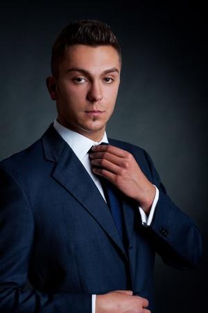 supervisi�n: hombre de modelo de moda joven ajustar su corbata