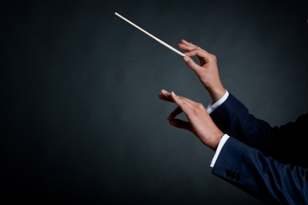 image of a male orchestra conductor directing with his baton in concert  photo