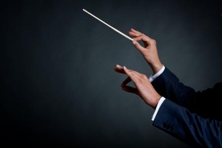 orquesta: imagen de un director de orquesta masculino dirigiendo con su batuta en concierto