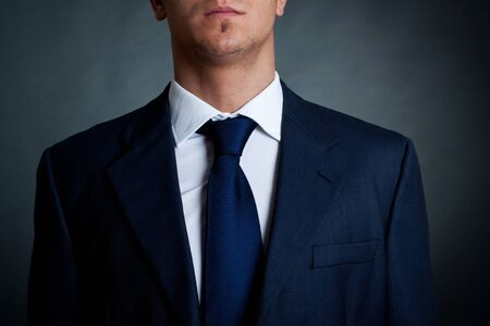 neck tie: Closeup shot of business suit on a man, over dark background