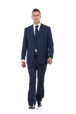 A young business man is walking. He is smiling and looking to the camera. isolated over white background Stock Photo - 9525319