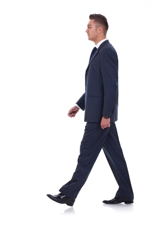 walking away: A young businessman is walking. He is smiling and looking away from the camera. isolated over white background