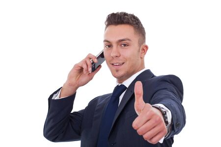 Business man making a thumbs up gesture, over white  photo