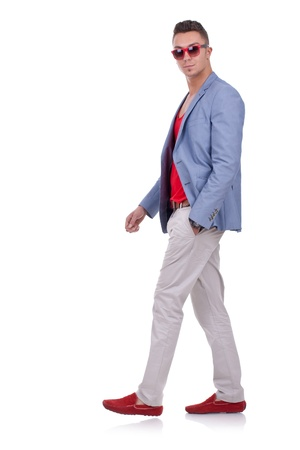 side view of a fashion man walking and looking at the camera photo