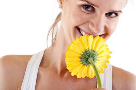picture of a pretty young woman smelling a yellow flower  photo