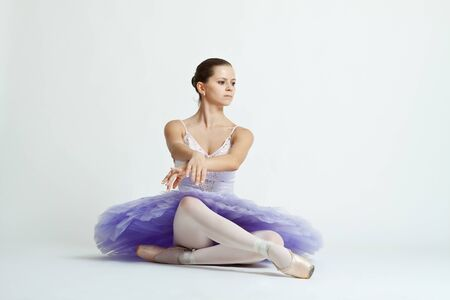 graceful ballet dancer with purple tutu sitting on studio background photo