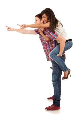 side pictureof a young man carrying his cute girl on back and pointing Stock Photo - 9730161