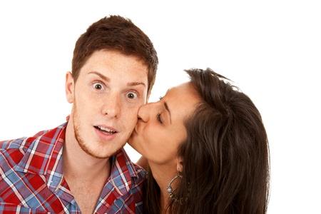 pretty young  woman kisses her boyfriend on the cheek  photo