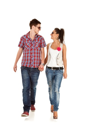 looking forward: Casual couple is walking towards the camera  on White, looking at each other