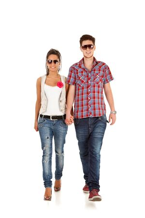 Young happy couple walking - full length portrait over white background  photo