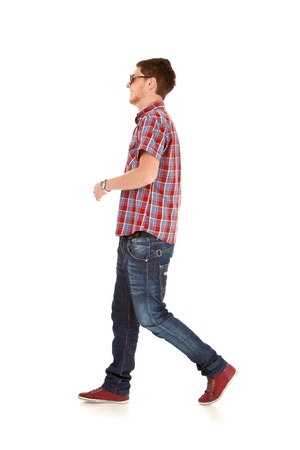 the walk: side view of a fashion man walking forward over white