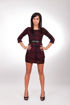 mujer cuerpo completo: Mujer joven de cuerpo completo en vestido rojo, aislado sobre un fondo gris.
