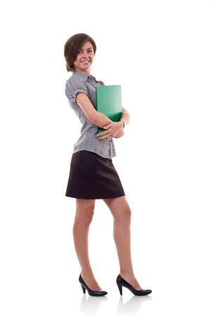 business woman standing: Portrait of a beautiful young business woman holding a folder, full length