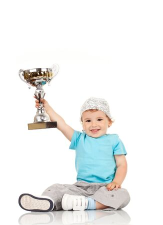 Portrait of a excited small boy holding a winners cup  photo
