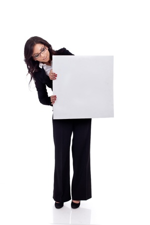 Portrait of a beautiful business woman holding a blank billboard, looking out from behind it.  Stock Photo - 9971776