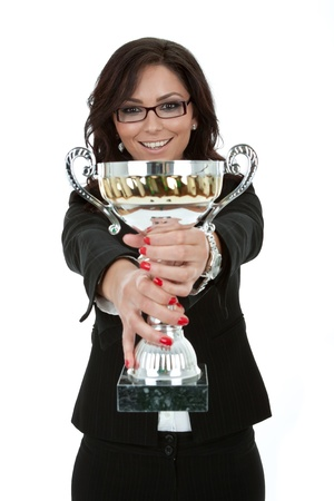 women holding cup: Portrait of a joyful young female entrepreneur holding a trophy against white background