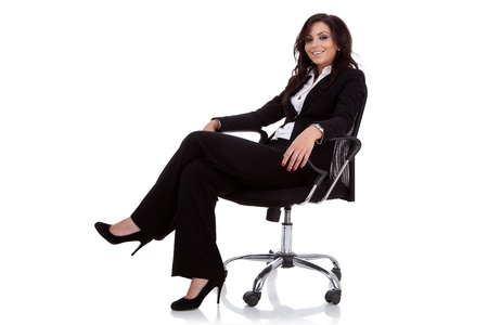 Young business woman sitting on a chair isolated on white  photo