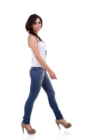side pose: Fashion girl wearing white shirt and jeans walking in studio