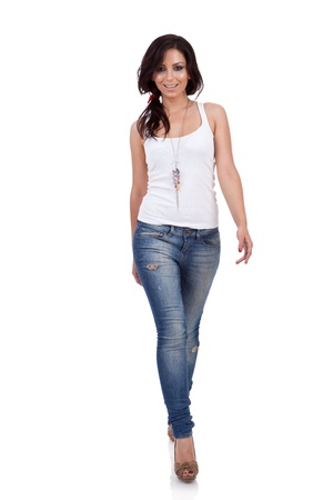 Fashion girl wearing white shirt and jeans walking in studio photo