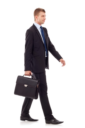 business man holding brief case and walking over white background photo
