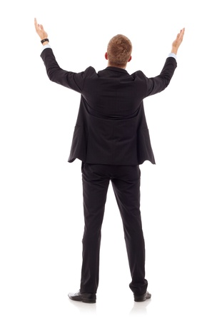 arms outstretched: business mans back praying with his arms up , over white  Stock Photo
