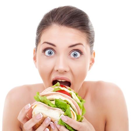 Woman with big round eyes eating a big yummy sandwich photo